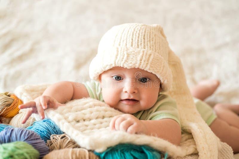 De leuke baby in een wit breide GLB met een bumbon op een rieten mand Multi-colored breiende draden vele verwarring stock fotografie