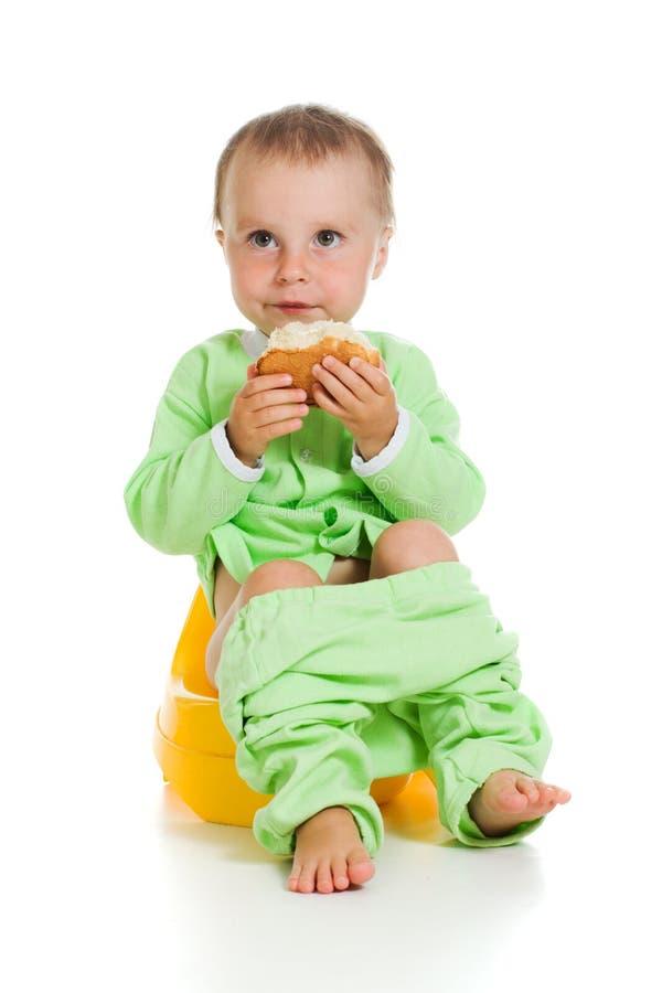 De leuke baby eet de broodzitting op de pot royalty-vrije stock fotografie