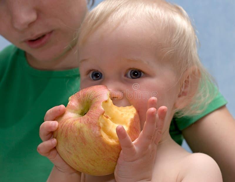 De leuke baby eet een appel stock foto