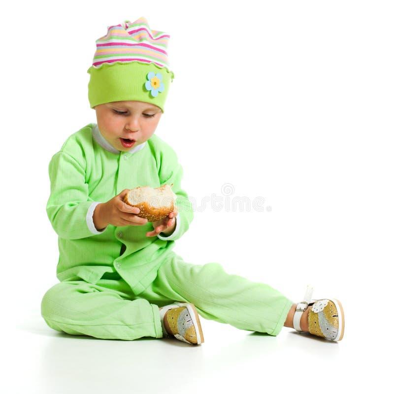 De leuke baby eet het brood stock afbeeldingen