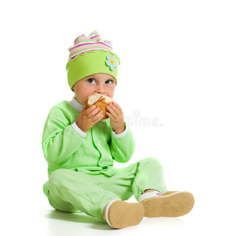De leuke baby eet het brood stock fotografie