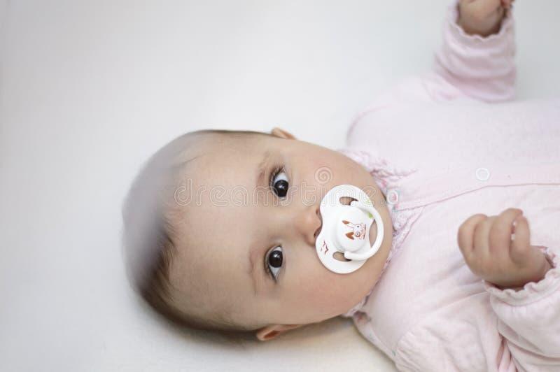 De leuke baby ligt in de voederbak met fopspeen stock afbeelding