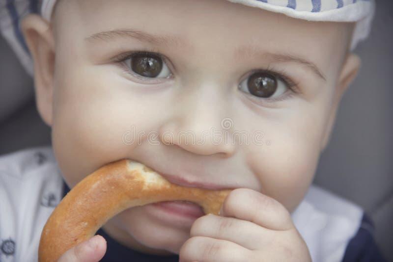 De leuke baby met een eetlust eet een ongezuurd broodje royalty-vrije stock fotografie