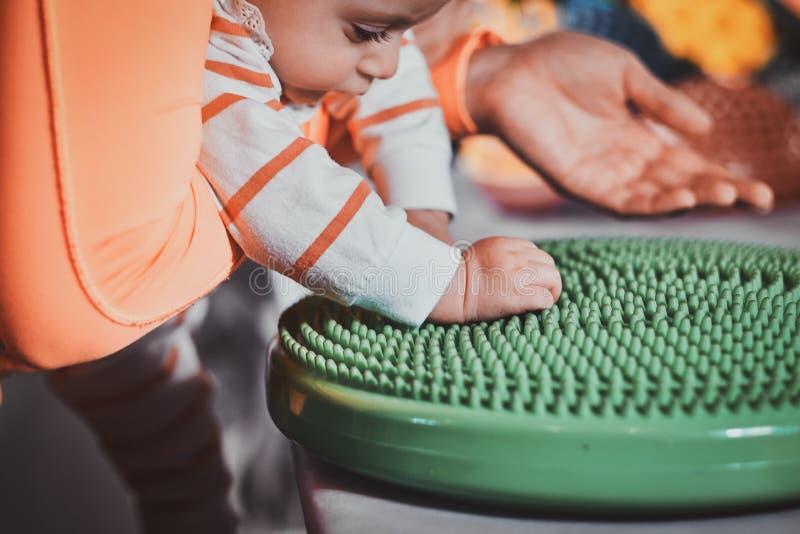 De leuke baby is nieuwsgierig over speciaal behandelingsstuk speelgoed royalty-vrije stock afbeeldingen