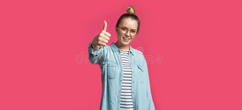 De leuke blonde vrouw toont geïsoleerde duim, stock foto