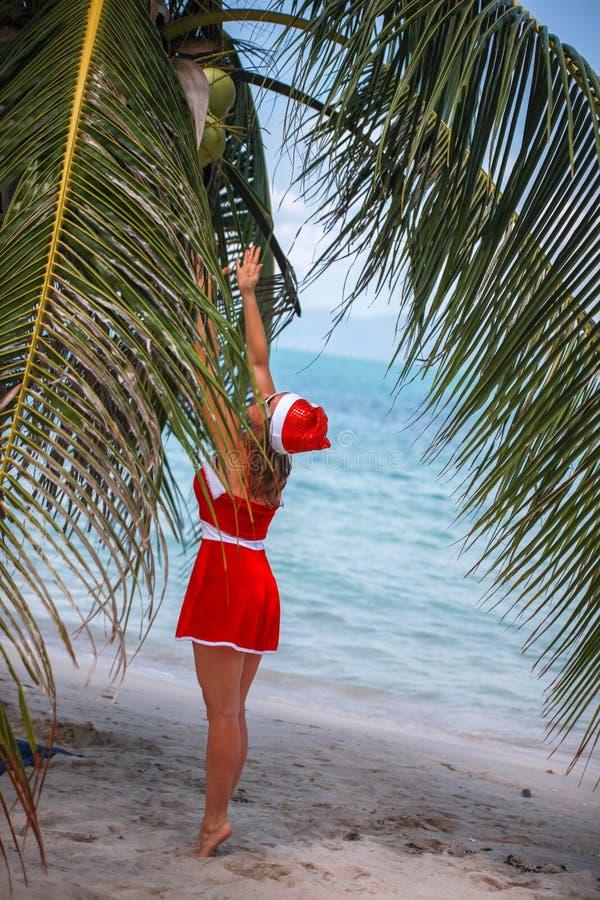 De leuke blondevrouw in rode kleding en santahoed springt aan palmenkokosnoot op exotisch tropisch strand Vakantieconcept voor stock fotografie