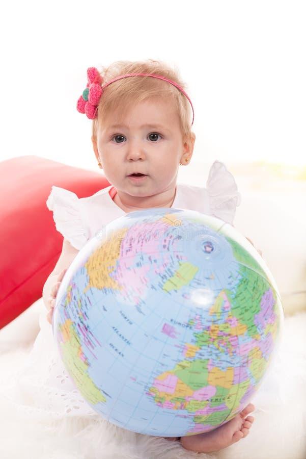 De leuke bol van de de holdingswereld van het babymeisje royalty-vrije stock foto's