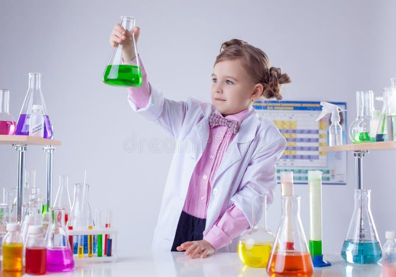 De leuke chemicus onderzoekt buizen met kleurrijke reagens stock foto