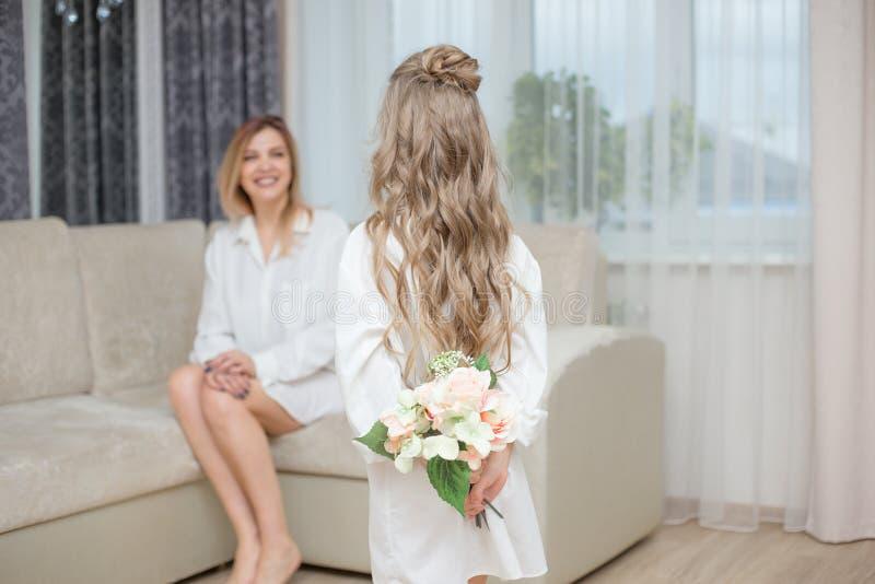 De leuke dochter geeft haar moederbloemen royalty-vrije stock afbeeldingen