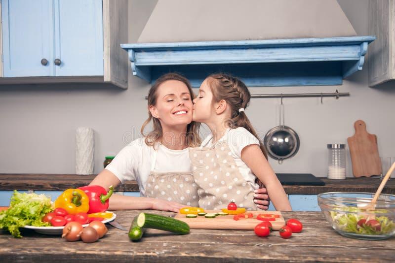 De leuke dochter kust mamma op haar wang terwijl het koken op een mooie blauwe keuken stock foto's