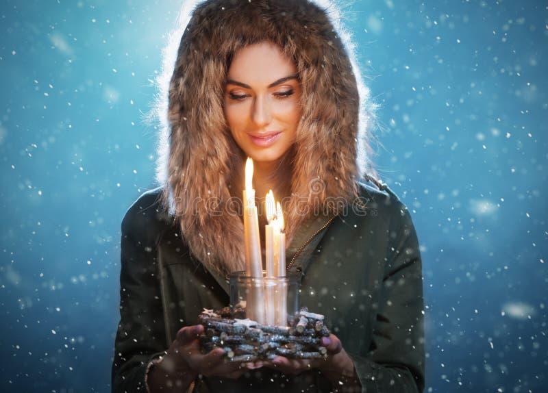 De leuke donkerbruine jonge kaarsen van de vrouwenholding stock afbeelding