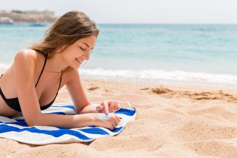 De leuke en glimlachende vrouw past zonnescherm op haar hand met de vinger toe zonnebadend op de handdoek bij het strand stock afbeelding
