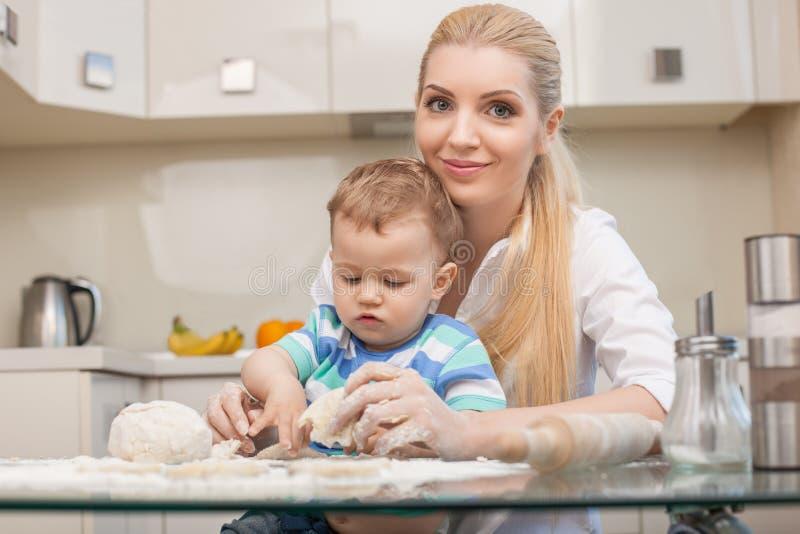 De leuke familie bakt smakelijke koekjes in stock afbeelding