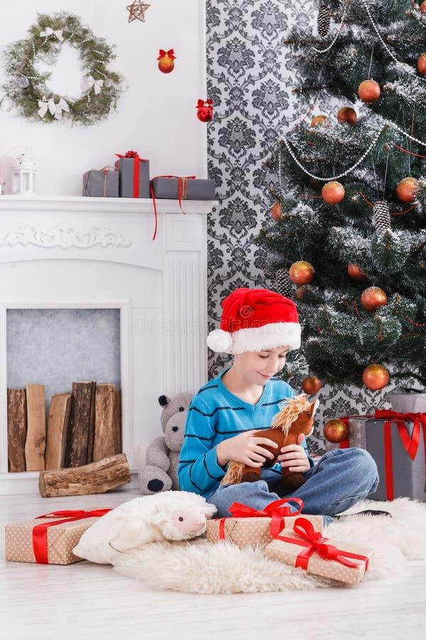 De leuke gelukkige jongen in santahoed met stuk speelgoed Kerstmis stelt voor stock fotografie