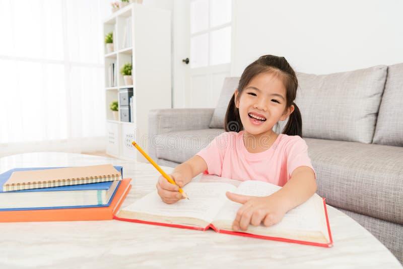 De leuke gelukkige student die van het meisjesjonge geitje bestuderend boek schrijven royalty-vrije stock foto's