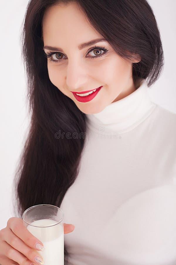 De leuke gezonde die vrouw is consumptiemelk van een glas op witte achtergrond wordt geïsoleerd royalty-vrije stock foto's
