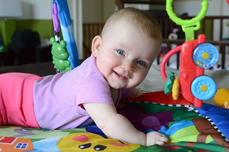 De leuke glimlachende Kaukasische baby legt op het bed Zij is gelukkig om met speelgoed rond haar te spelen royalty-vrije stock foto