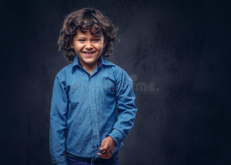 De leuke glimlachende schooljongen met bruin krullend haar kleedde zich in een blauw overhemd, die bij een studio stellen op gewe royalty-vrije stock fotografie