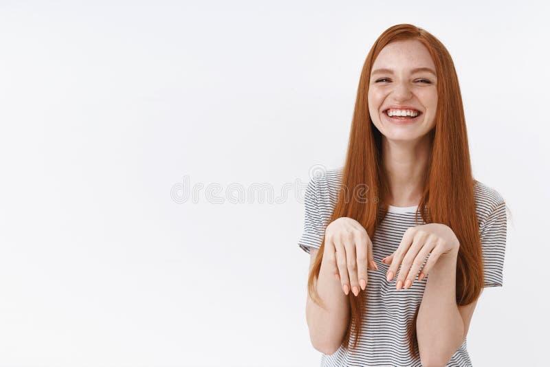 De leuke grappige mooie aantrekkelijke dwaas die van het roodharigemeisje rond van het de borstpuppy van verhogingspalmen de pote stock foto