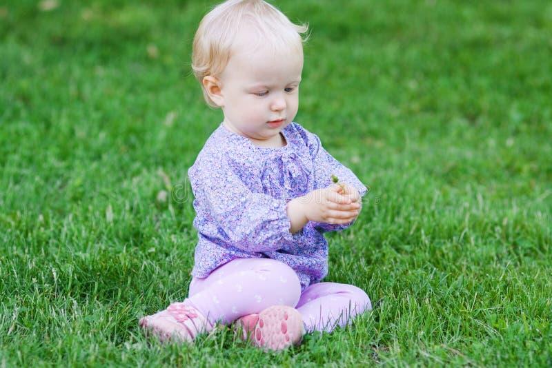 De leuke grappige zitting van het babymeisje op gras op een weide royalty-vrije stock fotografie