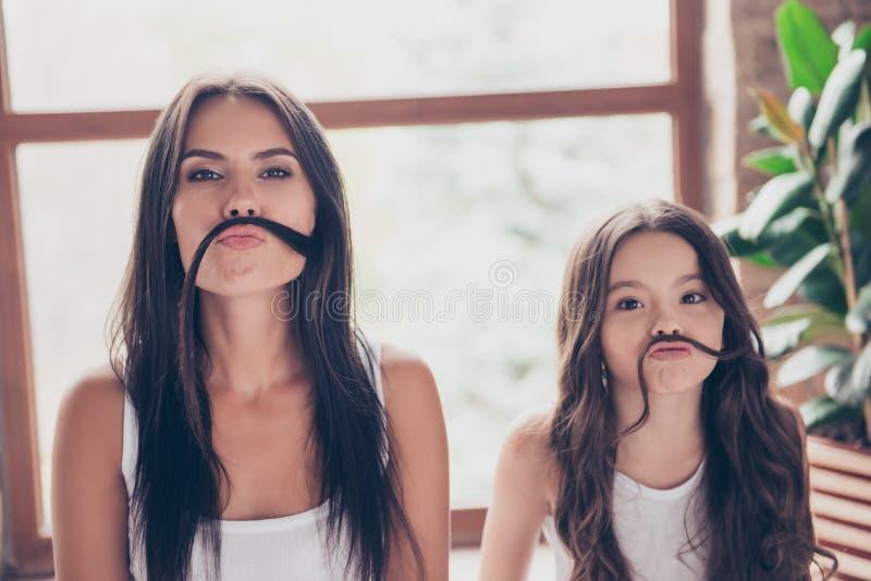 De leuke grappige zusters met mooi lang hdark haar maken fak stock afbeeldingen