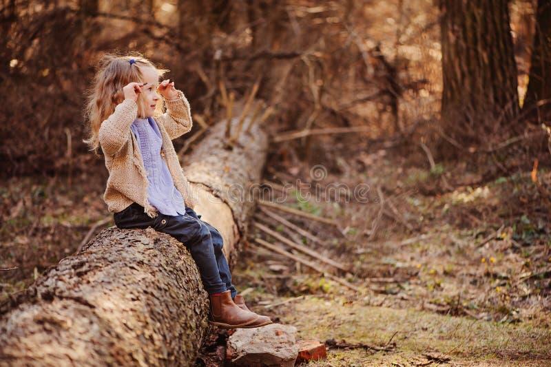 De leuke het glimlachen zitting van het kindmeisje op de boom in de lente zonnig bos stock foto