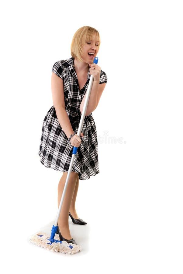 De leuke huisvrouw zingt aan bezemhandvat stock foto's