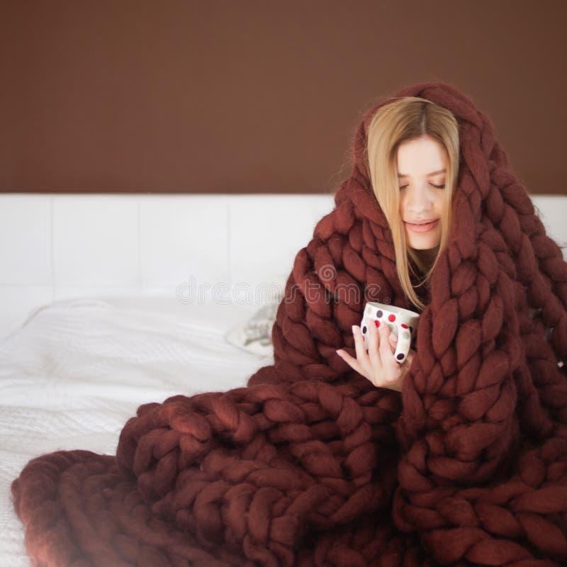 De leuke jonge die vrouw zit op het bed in een grote en pluizige bruine plaid wordt verpakt Warmte en comfort van huis stock foto's