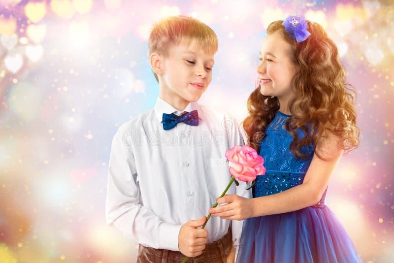 De leuke jonge geitjes, jongen geeft een bloemmeisje De dag van de valentijnskaart `s Kindliefde stock afbeeldingen