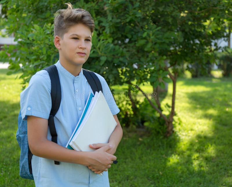 De leuke, jonge jongen in blauw overhemd met rugzak en de werkboeken in van hem dienen voorzijde van zijn school in Onderwijs, te royalty-vrije stock foto's