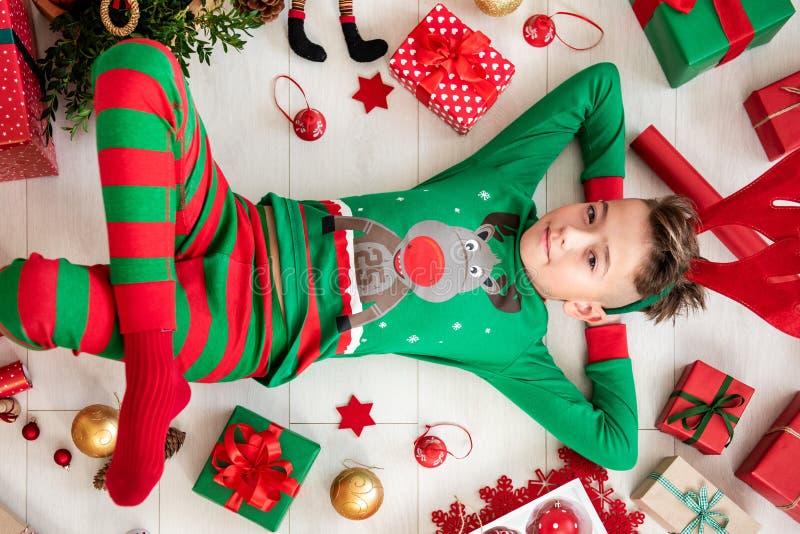 De leuke jonge jongen die Kerstmispyjama's dragen die die op de vloer liggen, door Kerstmis wordt omringd stelt voor, siert en de royalty-vrije stock foto