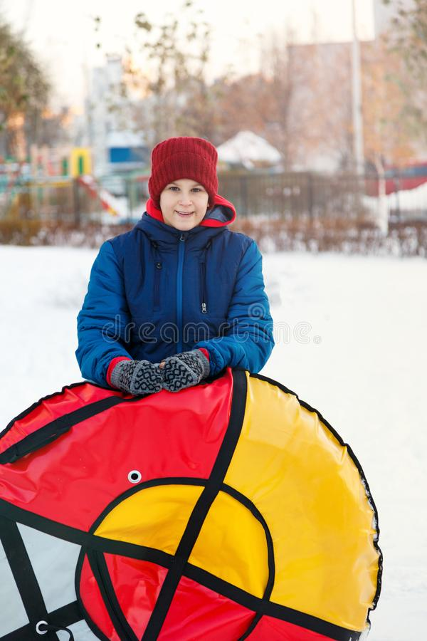 De leuke jonge jongen in hoed de matroos houdt en met sneeuw speelt, heeft pret, glimlachen, maakt sneeuwman in de winterpark Act stock afbeeldingen
