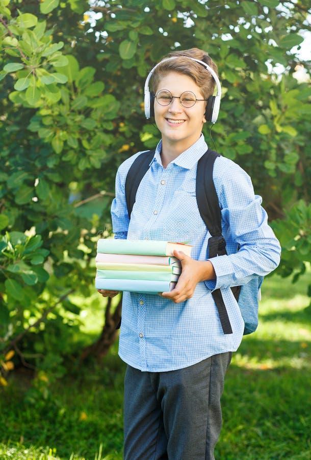 De leuke, jonge jongen in ronde glazen en het blauwe overhemd houden de boeken met van hem het park indient Het lezen en het lere stock foto's