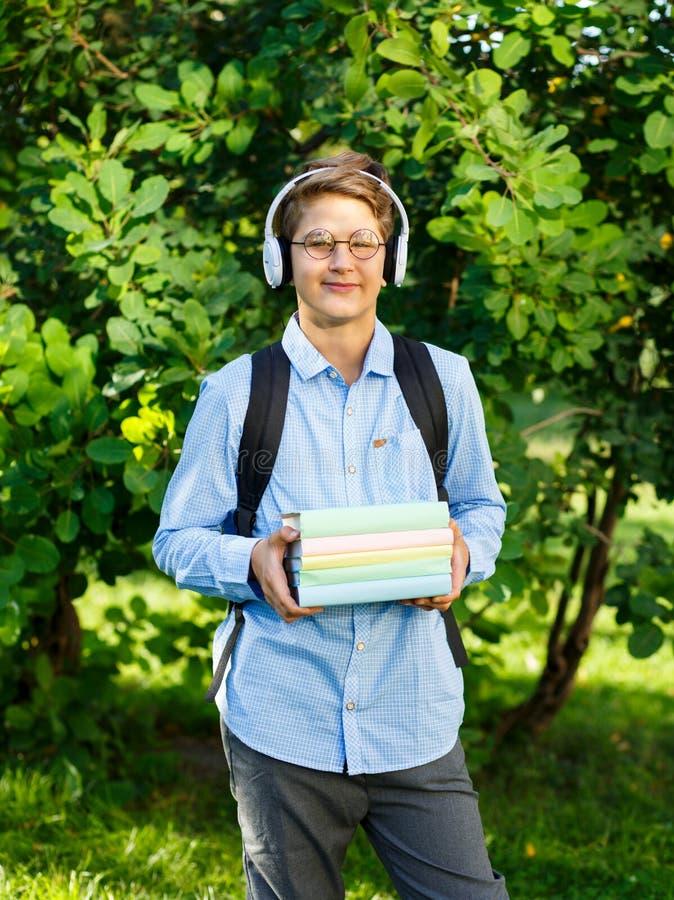 De leuke, jonge jongen in ronde glazen en het blauwe overhemd houden de boeken met van hem het park indient Het lezen en het lere royalty-vrije stock foto