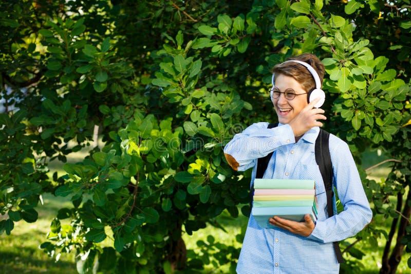 De leuke, jonge jongen in ronde glazen en het blauwe overhemd houden de boeken met van hem het park indient Het lezen en het lere stock foto