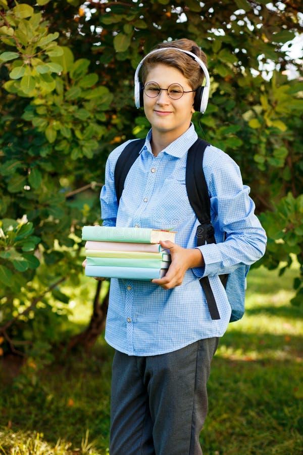 De leuke, jonge jongen in ronde glazen en het blauwe overhemd houden de boeken met van hem het park indient Het lezen en het lere stock fotografie