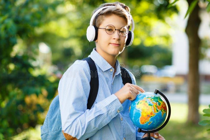 De leuke, jonge jongen in ronde glazen en het blauwe overhemd houden de boeken met van hem het park indient Het lezen en het lere stock afbeeldingen