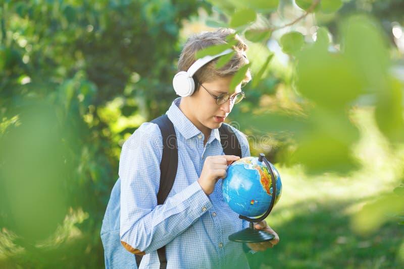De leuke, jonge jongen in ronde glazen en het blauwe overhemd houden de boeken met van hem het park indient Het lezen en het lere stock afbeelding