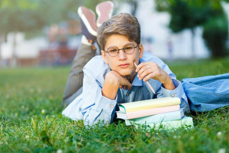 De leuke, jonge jongen in ronde glazen en het blauwe overhemd lezen boek op het gras in het park Onderwijs, terug naar school royalty-vrije stock foto's