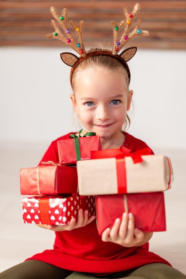 De leuke jonge stapel van de meisjesholding van Kerstmis stelt voor, glimlachend en bekijkend camera Gelukkig jong geitje bij Ker stock foto