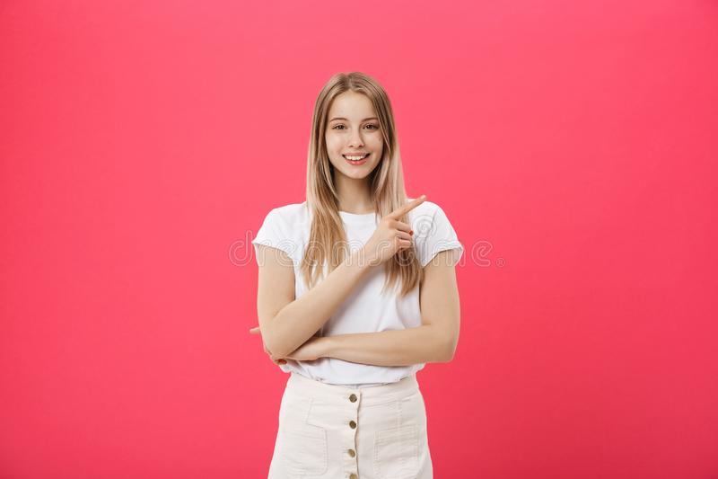 De leuke jonge vrouw die witte die t-shirt dragen richt een vinger weg over roze achtergrond wordt geïsoleerd royalty-vrije stock afbeeldingen