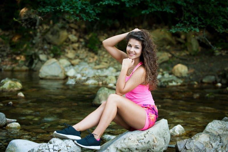 De leuke jonge vrouw rust achterin op een rots in rivierbed op de recente zomer royalty-vrije stock fotografie