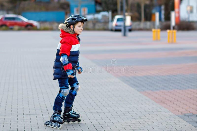 De leuke jongen die van het schooljonge geitje met rollen in de stad schaatsen Gelukkig gezond kind die in de kleren van de besch royalty-vrije stock foto