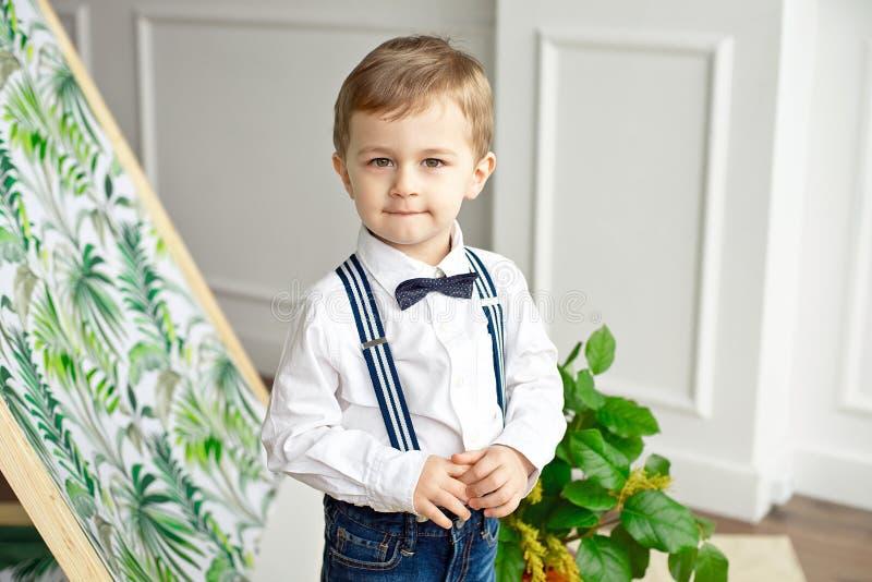 De leuke jongen in een witte overhemd en een vlinderdas bevindt zich in een ruimte dichtbij de tent met een glimlach stock afbeeldingen