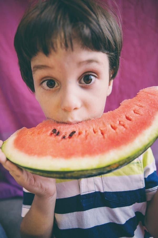 De leuke jongen eet een watermeloen stock foto's