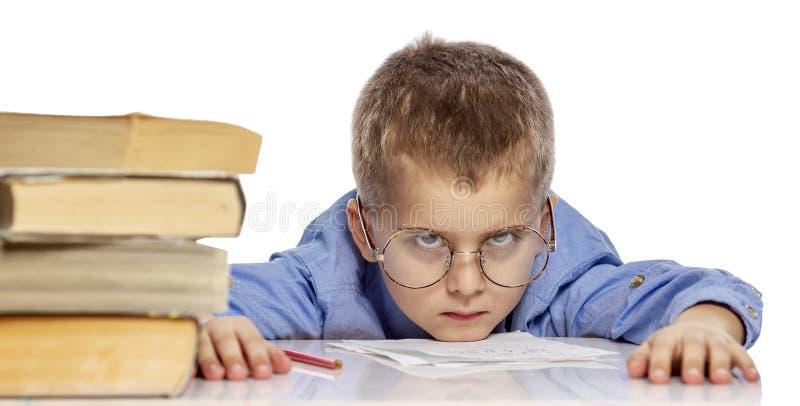 De leuke jongen in glazen van schoolleeftijd is vermoeid van het leren Ik hing mijn hoofd op handboeken Close-up Ge?soleerd op ee stock fotografie