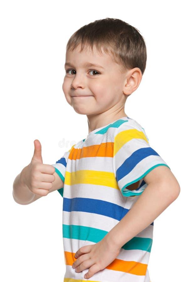 De leuke jongen houdt zijn duim tegen stock fotografie
