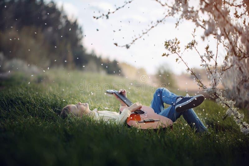 De leuke jongen ligt op het gras met een gitaar op zonsondergang royalty-vrije stock fotografie