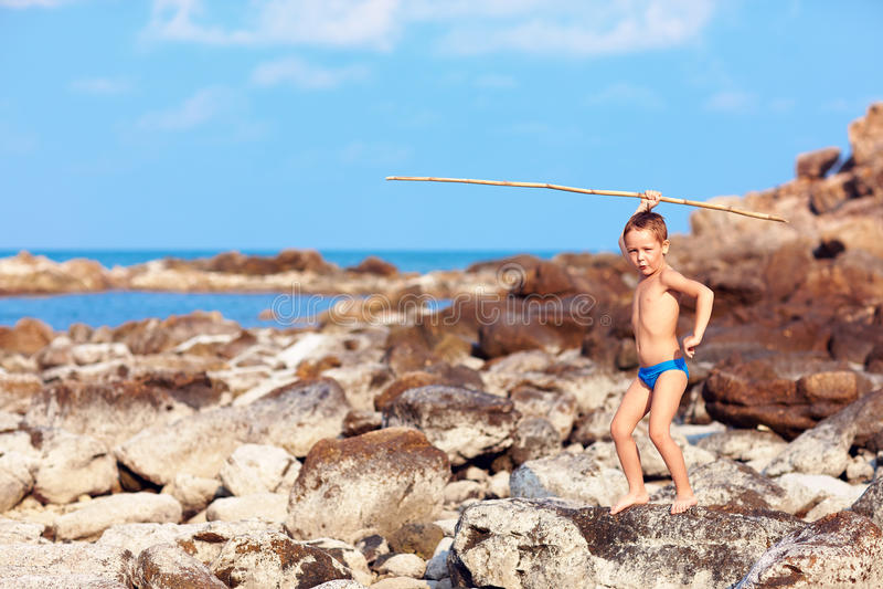 De leuke jongen met bamboespear beweert als hij is inboorling op woestijneiland stock foto