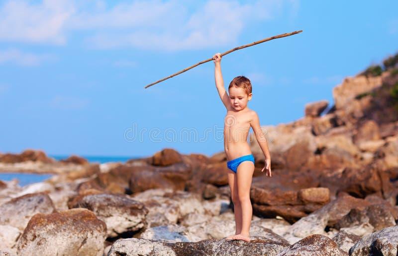 De leuke jongen met bamboespear beweert als hij is inboorling op woestijneiland stock foto's